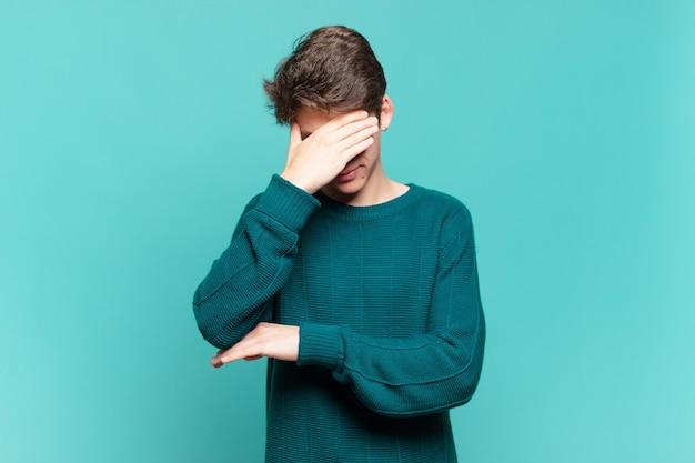 ストレス、恥ずかしがり屋、または動揺して、頭痛で、手で顔を覆っている少年