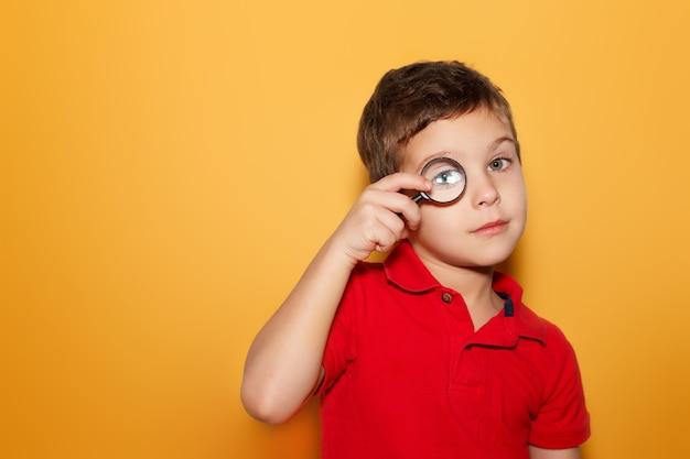 노란색 바탕에 돋보기를 통해 보는 어린 소년. 텍스트를위한 공간