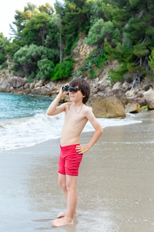 A young boy looking through binoculars staying at the seaside on the beach