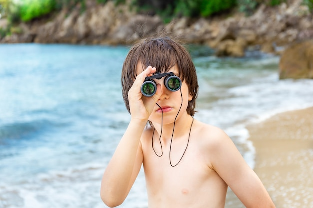 A young boy looking through binoculars staying at the seaside on the beach.