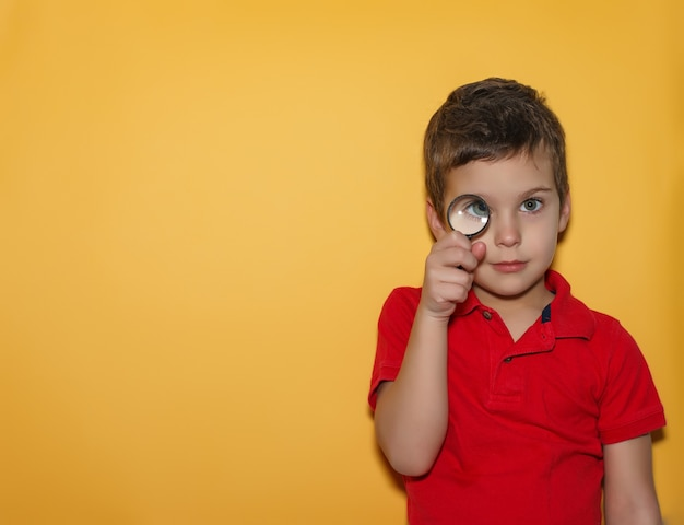 Young boy looking through a magnifying glass on yellow background. space for text