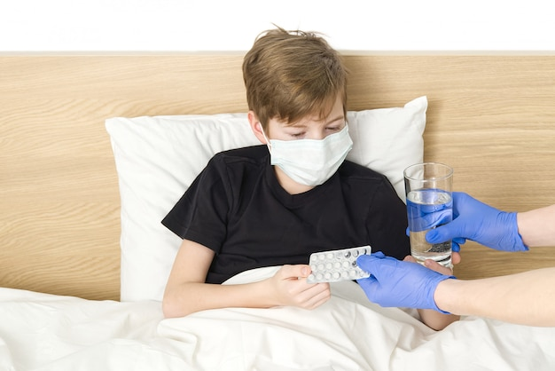 Young boy lying on the bed wearing medical mask