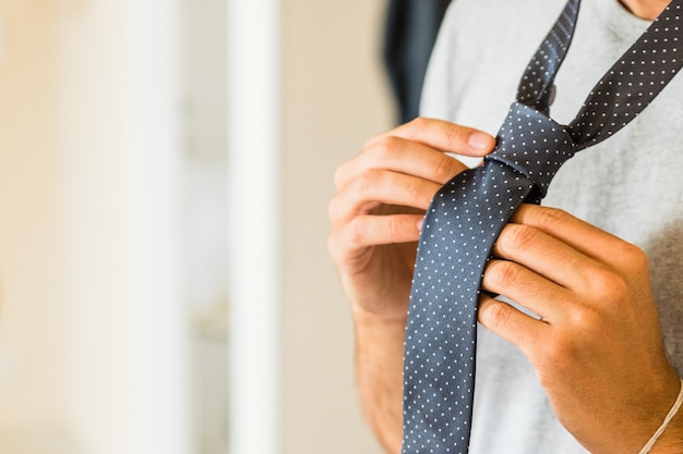Young boy making tie knot