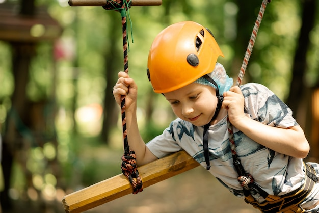 A young boy in a mountain belay and a flip flop goes through an obstacle course. active, sporty activity in the summer for a child.