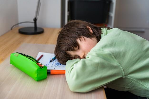 Мальчик десяти лет делает домашнее задание, сидя за столом у себя дома. усталый ребенок спит, когда делает школьные упражнения лицом на парту.