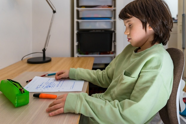 Мальчик десяти лет делает домашнее задание, сидя за столом у себя дома. усталый ребенок засыпает, когда делает школьные упражнения.