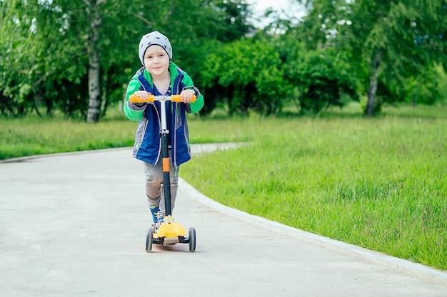 푸른 잔디와 나무의 배경에 공원에서 스쿠터에 어린 소년