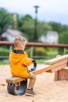 Мальчик на качелях в одиночестве качается в парке, выстрел сзади