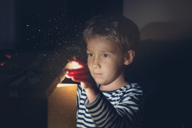 Мальчик открывает золотую подарочную коробку с искрящимся светом и сияющими от нее блестками
