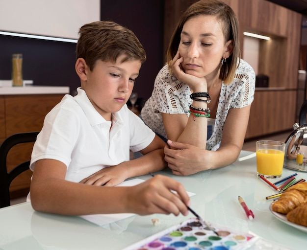 Young boy painting while his mother is checking