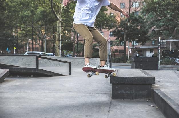 Молодой мальчик, выполняя трюки с скейтборд в скейт-парк