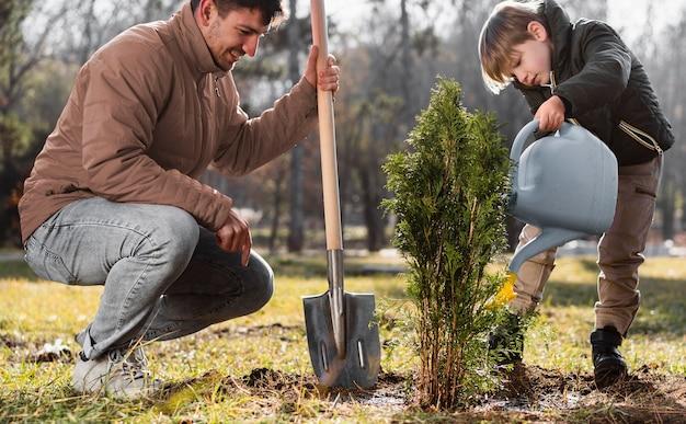 Молодой мальчик сажает дерево на открытом воздухе и использует лейку