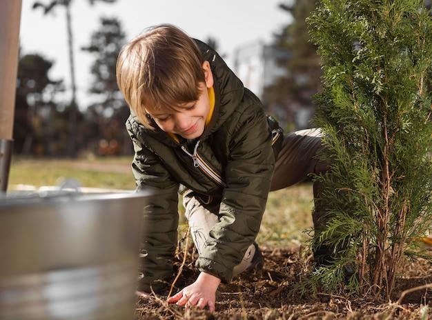 Мальчик сажает дерево на улице