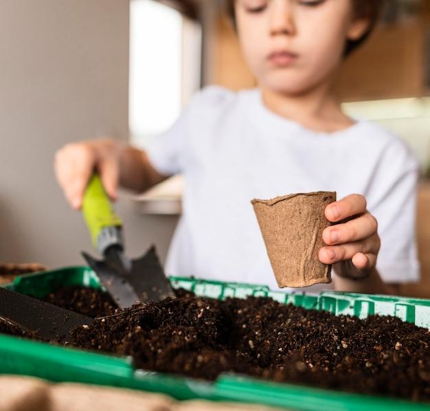 집에서 작물을 재배하는 어린 소년