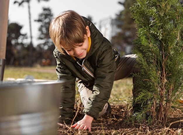 Young boy planting a tree outside