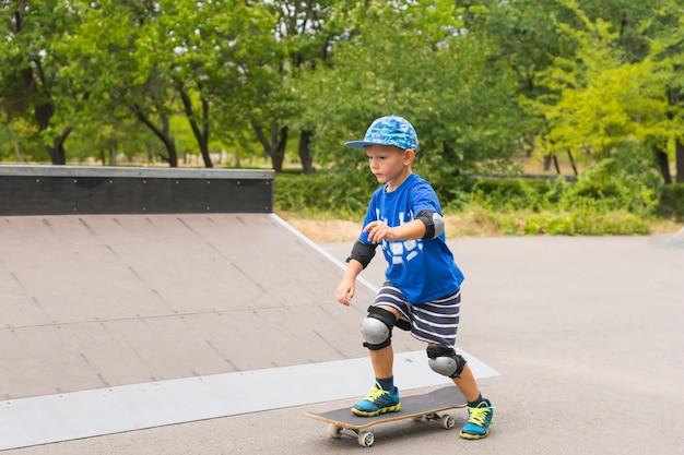 膝と肘のパッドを備えたトレンディな青い服でバランスを練習しながら、スケートボードのスケートパークで遊んでいる少年