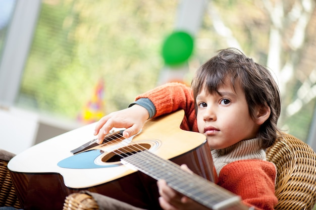 Young boy playing on the guitar