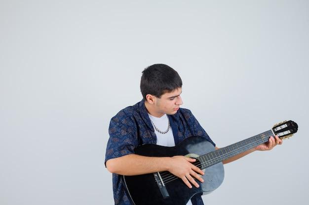 Молодой мальчик играет гитара в футболке и выглядит уверенно. передний план.