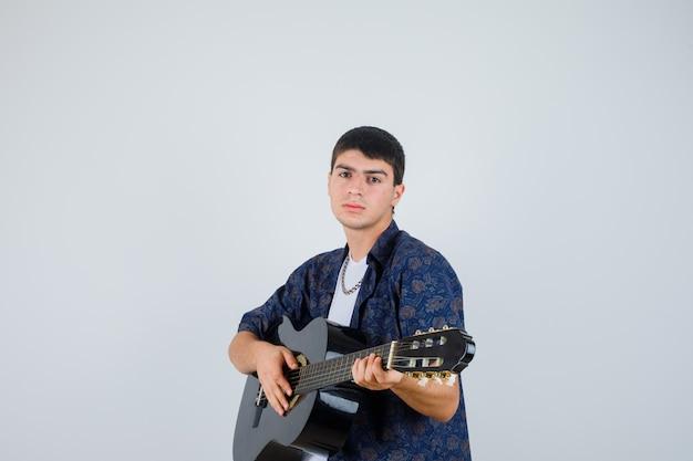 Молодой мальчик играет гитара, глядя на камеру в футболке и выглядит уверенно, вид спереди.