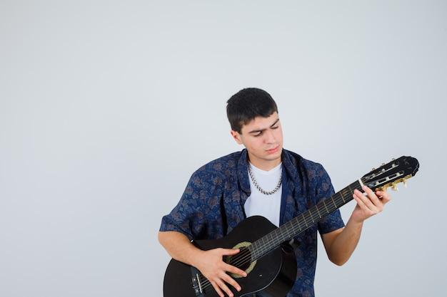 Молодой мальчик играет на гитарах, сидя на гитаре в футболке и выглядит уверенно, вид спереди.