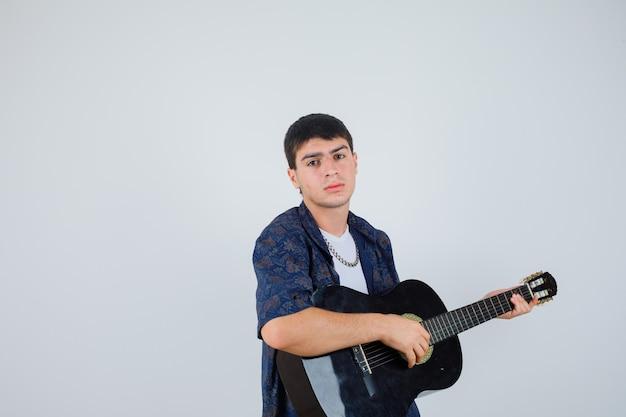 Молодой мальчик играет на гитарах, сидя на аганисте, глядя в камеру в футболке и выглядит уверенно. передний план.