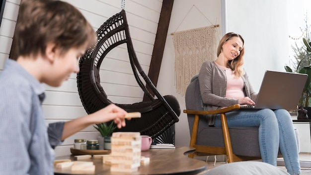 Young boy playing jenga while mom is working