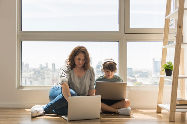 Young boy playing on laptop next to mom