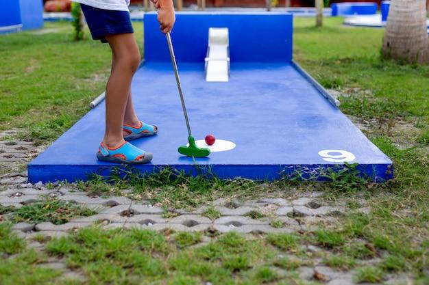 Young boy playing mini golf