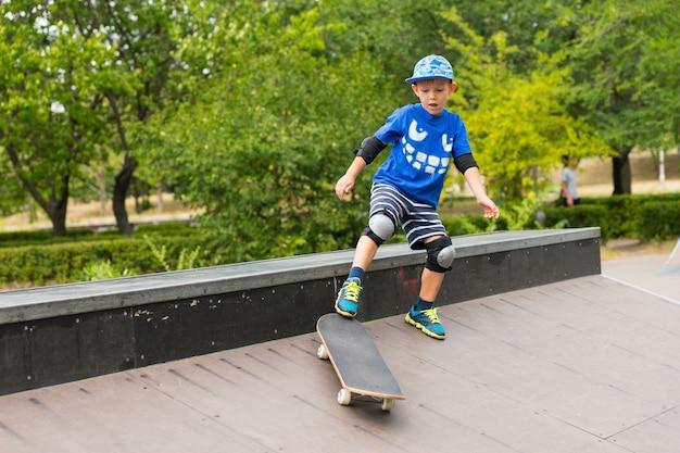 屋外でスケートボードで遊んでいる少年は、スケートパークのコンクリートのスロープの頂上でジャンプします。