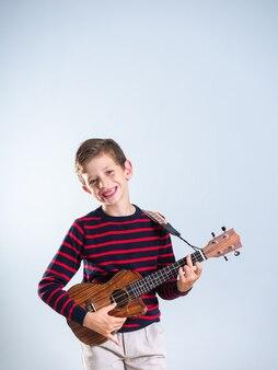 Молодой мальчик играет на укелеле, его передние зубы отсутствуют, изолированные на сером фоне, с копией пространства