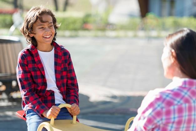 Мальчик играет с матерью в парке