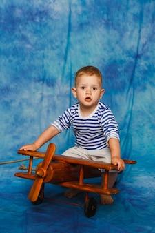 Мальчик играет с игрушечным самолетиком