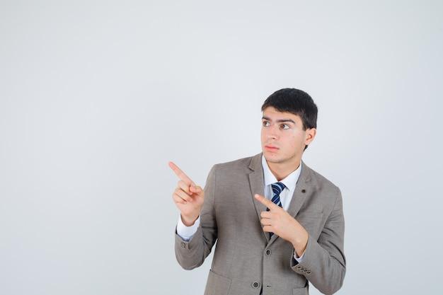 Молодой мальчик, указывая влево указательными пальцами в строгом костюме и серьезный вид спереди.
