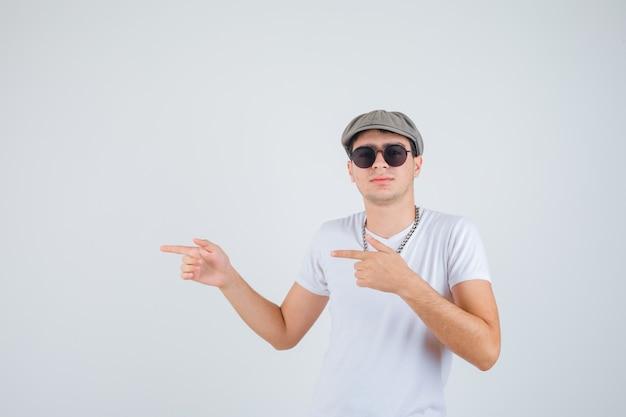 Tシャツ、帽子、自信を持って左側を指している少年。正面図。