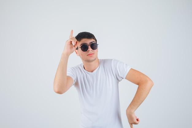 T- 셔츠에서 가리키는 자신감, 전면보기를 찾고 어린 소년.