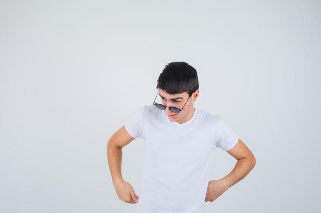 T- 셔츠에서 옆으로보고 자신감을 찾고있는 동안 포즈를 취하는 어린 소년. 전면보기.