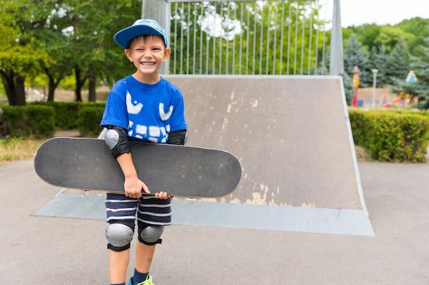 公園でスケートボードを腕に抱えてポーズをとっている少年が、カメラに明るい笑顔を与え、バックグラウンドで傾斜している
