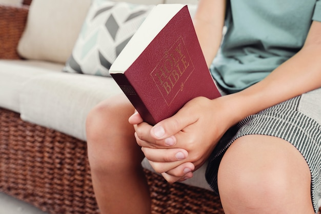 Young boy praying hands over a bible book