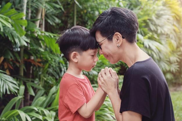 屋外の公園で彼の母親と一緒に祈る少年