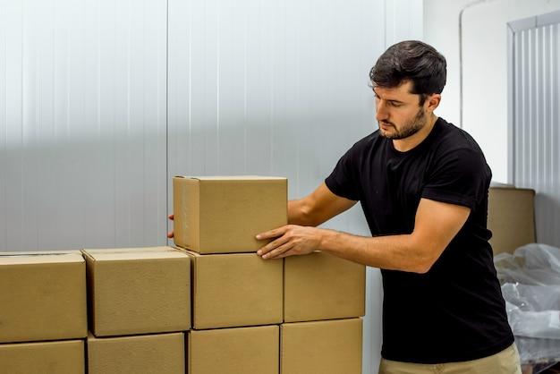 Молодой мальчик готовит поставки в картонных коробках на фабрике