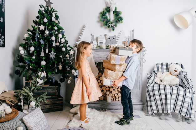 Young boy presenting gift boxes to pretty little girl in room with cristmas tree and fireplace. winter holidays.