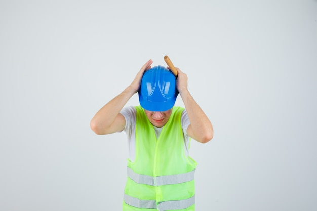 Young boy pressing hands on ears, holding hammer in construction uniform and looking harried. front view.