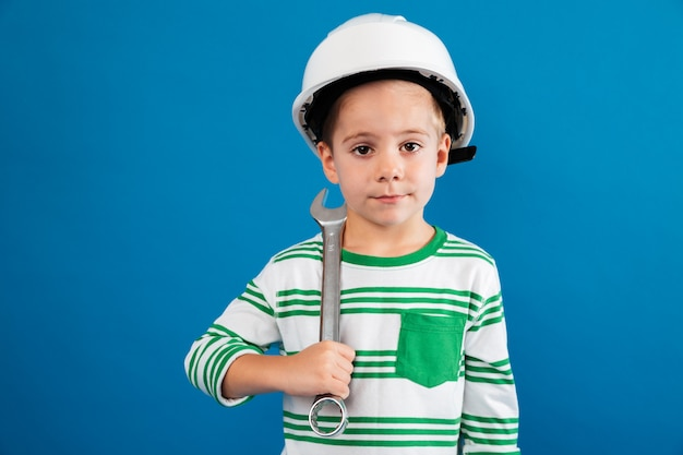 Young boy in protective helmet posing with wrench