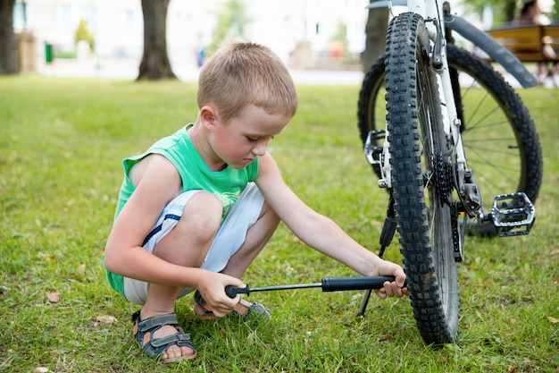 Young boy pumping the bicycle tube