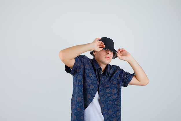 Young boy putting hands on cap in white t-shirt, floral shirt, cap and looking confident. front view.