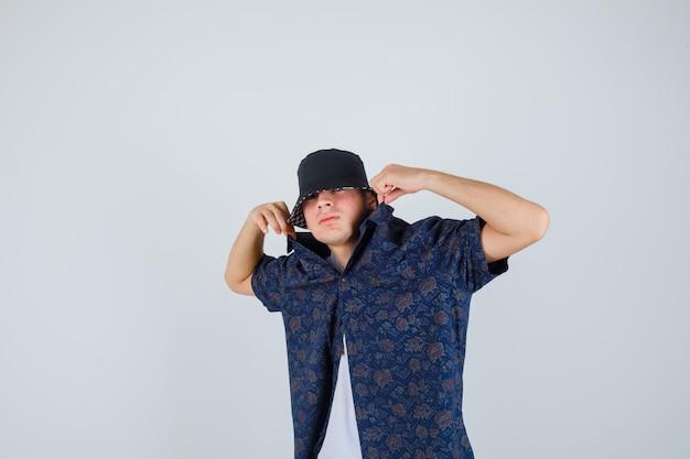 Ragazzo che mette le mani sui colletti della camicia in maglietta bianca, camicia floreale, berretto e sembra fiducioso. vista frontale.