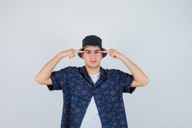 白いtシャツ、花柄のシャツ、キャップで寺院に人差し指を置き、自信を持って見える少年。正面図。