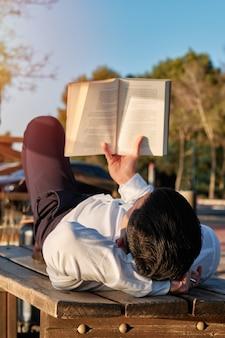 日光の下で本を読んでいる少年
