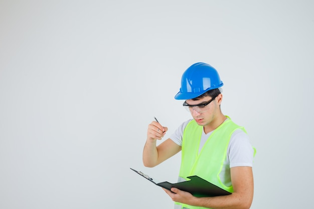 Young boy reading notes in file folder while holding pen in construction uniform and looking focused , front view.
