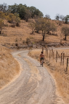 Young boy rides a bicycle on a dirt road